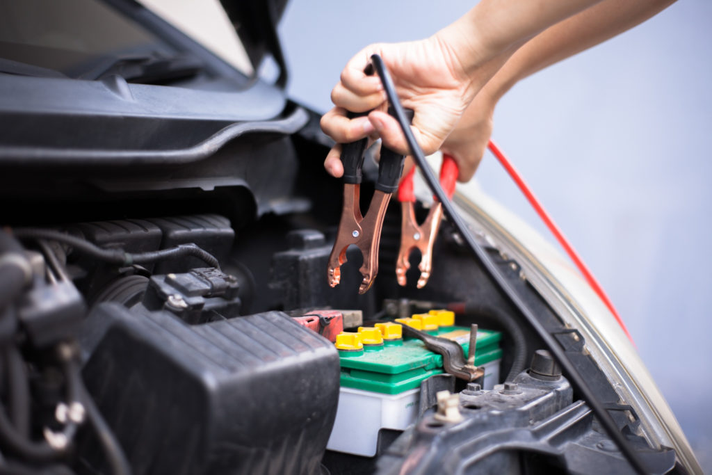 Mechanic Holding Battery Charging Cables
